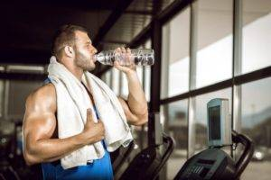 Мужчина в спортзале пьет воду