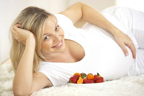 young pregnant woman with fresh fruits