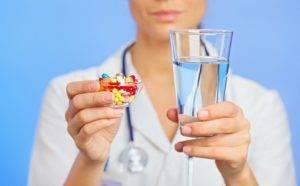 Врач держит в руках стакан с водой и таблетки